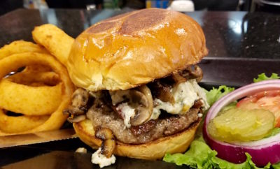 Build Your Own Burger with 44 Farms Burger with aged Blue Cheese, Mushrooms, Peppered Bacon on a Brioche Bun with a side of hand battered onion rings at Omega Grill