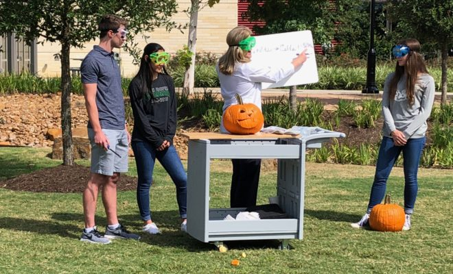 """Chemistry teacher Cathy Mock surprised STEM Society students at The John Cooper School with a science experiment that """"self-carved"""" Halloween pumpkins."""
